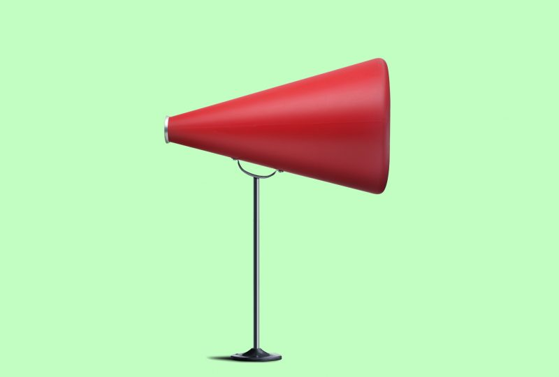 A profile view of a red megaphone on a tall stand against a green background.
